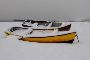 Boats on the snowy beach by Ivana Vavreckova
