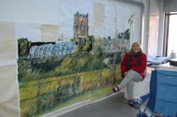 Photograph of Sue Daniels with one of her paintings