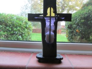 Crucifix with stained glass backing on iron base with candle holder behind by stella