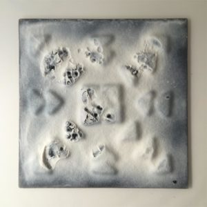 Manhole with snowy bootprints by Lois Parker