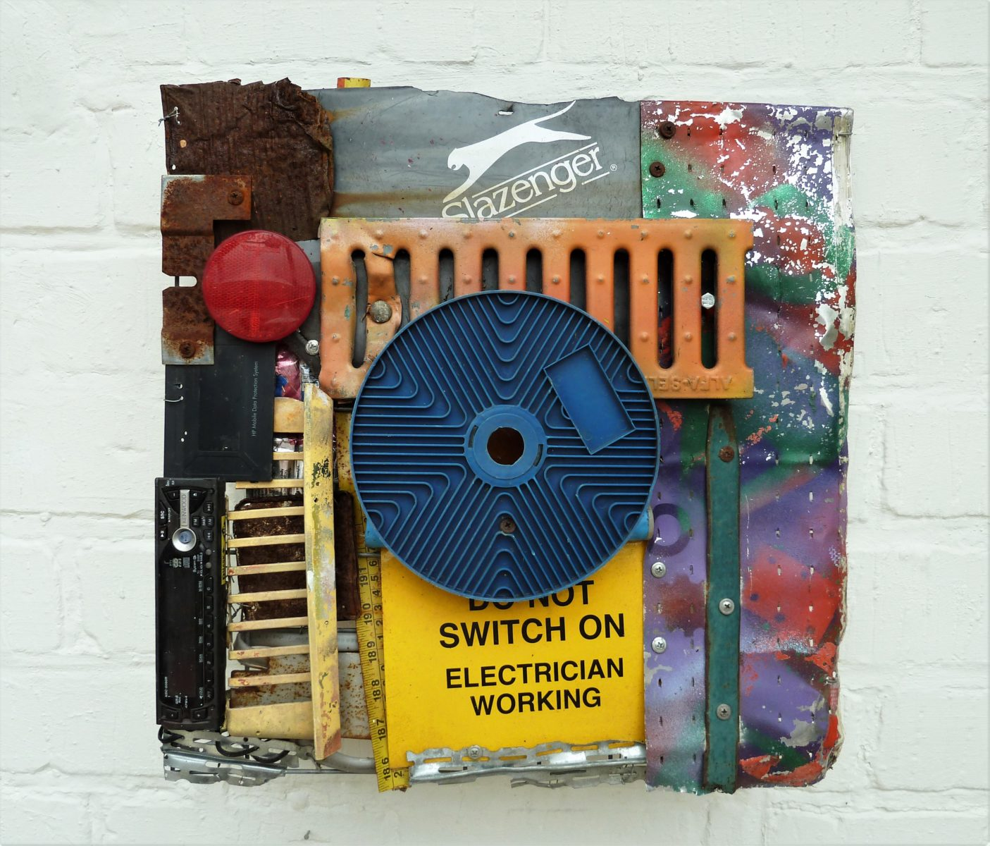 sculpture using metal objects including grill, slazenger icon and don not switch on sign