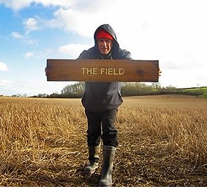 Photograph pf a person in a corn field with a The field sign