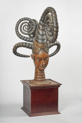 Ekoi headdress, dates from the late 19th century. Carved wooden head with big spirals of braids , mounted on a wooden box.